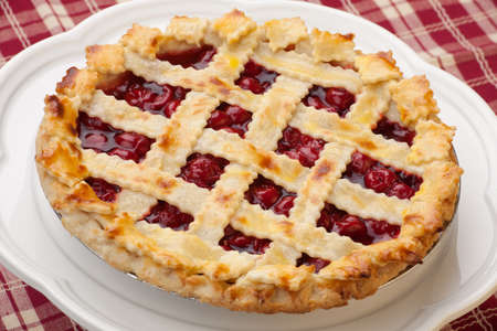 Cherry pie with lattice top on fall themed napkin, and mini pumpkins  Stock Photo - 17618176