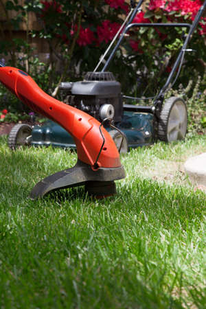 electric trimmer: Woman is trimming her lawn with electric edge trimmer