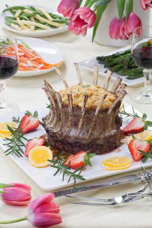 stuffing: Crown roast of lamb with apple rosemary stuffing  Garnished with fresh strawberry, lemon, and rosemary twigs  Side dishes - asparagus, glazed carrots, and beans  Stock Photo