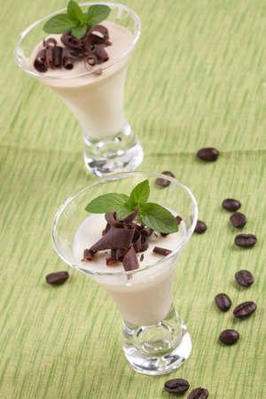 Closeup of Coffee Vanilla Panna Cotta Dessert in glass garnished with dark chocolate shavings, and fresh mint  photo