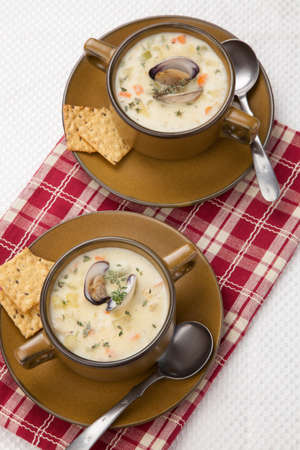 multy: Bowls of hot delicious clam chowder garnished with fresh thyme, and multy grain crackers Stock Photo