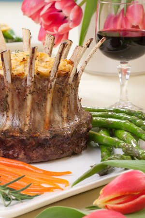 Crown roast of lamb with apple rosemary stuffing  Garnished with asparagus, glazed carrots, and rosemary twigs  Side dishes - asparagus, and beans Stock Photo - 18236242