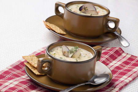 Bowls of hot delicious clam chowder garnished with fresh thyme, and multy grain crackers Stock Photo - 18378299