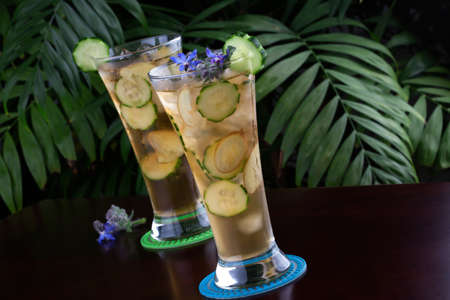 non: Two glasses of ginger and cucumber iced tea garnished with borage flowers on a table in a restaurant on a tropical beach