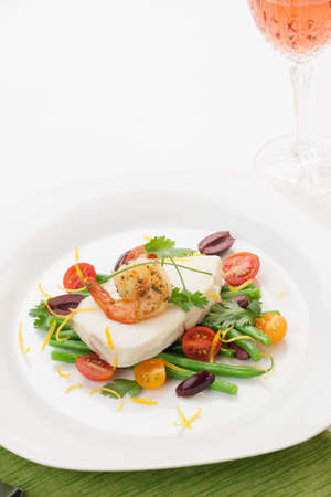Poached halibut with spicy shrimp, green beans, cherry tomatoes, black olives, and citrus sauce.  photo