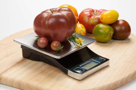 Digital kitchen scale on table surrounded with fresh tomatoes, and basil.  photo