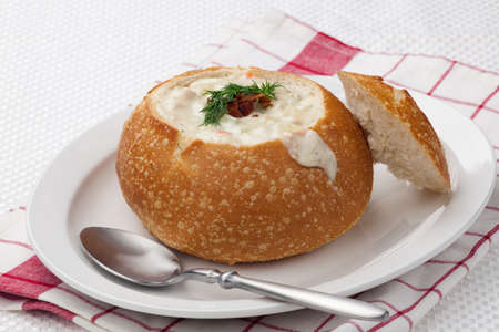 Sourdough bun of delicious hot clam chowder garnished with bacon, and dill