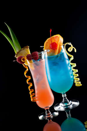 shaken: Rum Runner and Blue Lagoon cocktaisl over black background on reflection surface