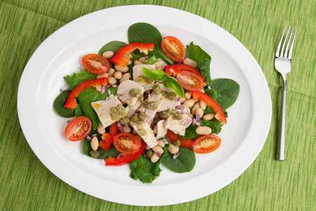 Tuna salad with fresh spinach, cherry tomatoes, white beans and pesto dressing