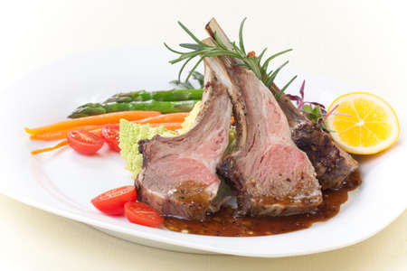 Rosemary roasted lamb chops  ribs  garnished with asparagus, glazed carrots,, grape tomatoes, and micro greeens