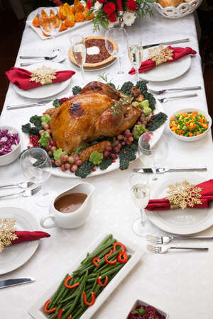 Holiday-decorated table, Christmas tree, champagne, and roasted turkey  Stock Photo - 19123190