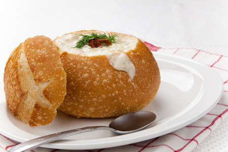 Sourdough bun of delicious hot clam chowder garnished with bacon, and dill  photo