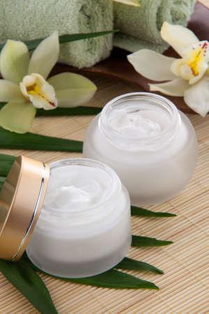 cremas faciales: Blanca flor de la orquídea Cymbidium y tarro de crema facial hidratante para tratamiento de spa Foto de archivo