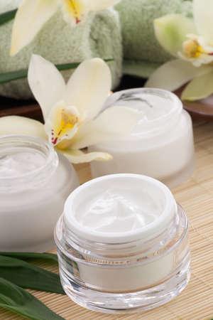 cremas faciales: Blanca flor de la orqu?dea Cymbidium y tarro de crema hidratante cara para tratamiento de spa Foto de archivo