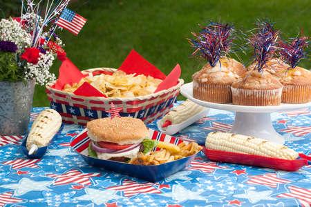 Maisbrot, Mais und Burger am 4. Juli Picknick in patriotischen Thema Standard-Bild