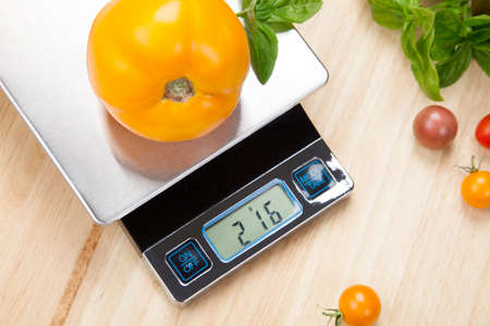 kitchen scale: Digital kitchen scale on table surrounded with fresh tomatoes, and basil  Stock Photo