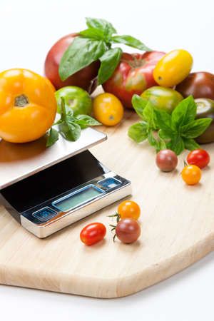 Digital kitchen scale on table surrounded with fresh tomatoes, and basil  Stock Photo
