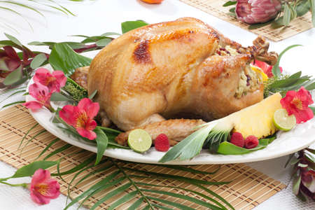Garnished roasted turkey with tropical fruits, flowers, and refreshing cocktails  Stock Photo - 19586664