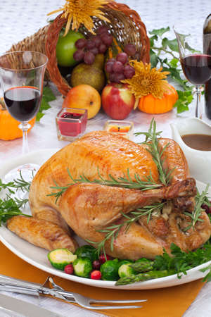 horn of plenty: Garnished roasted turkey on fall festival decorated table with horn of plenty and red wine Stock Photo