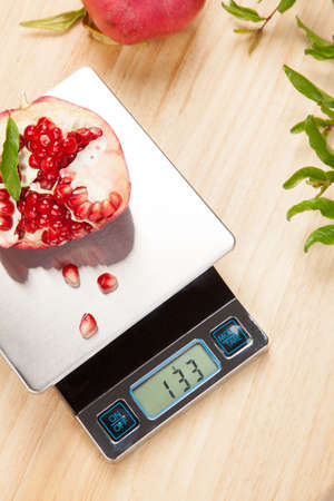kitchen scale: Digital kitchen scale on table and pomegranate