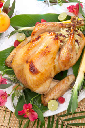 Garnished roasted turkey with tropical fruits, flowers, and refreshing cocktails