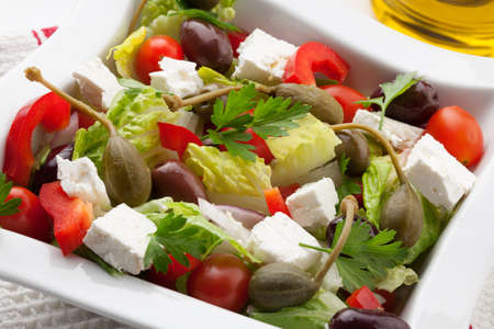 feta cheese: Refreshing crispy Greek salad with cherry tomatoes, olives, bell pepper, caperberries, and feta cheese