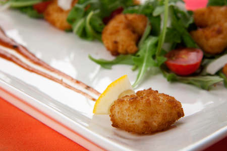 Popcorn shrimp and baby arugula salad with grape tomatoes and white sweet onions  Imagens
