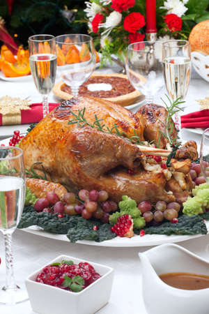 Holiday-decorated table, Christmas tree, champagne, and roasted turkey  Stock Photo - 20705194