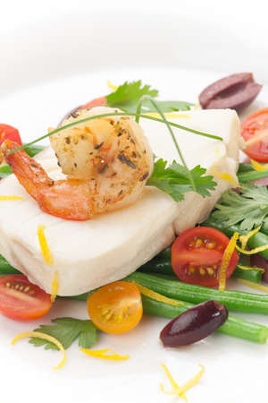 Poached halibut with spicy shrimp, green beans, cherry tomatoes, black olives, and citrus sauce  photo