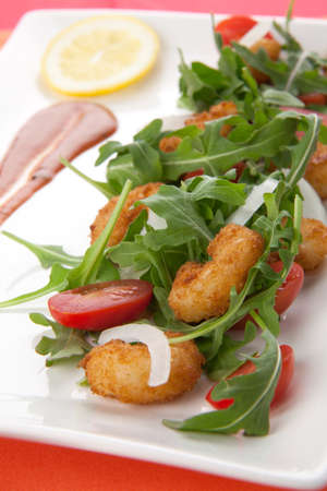 Popcorn shrimp and baby arugula salad with grape tomatoes and white sweet onions.