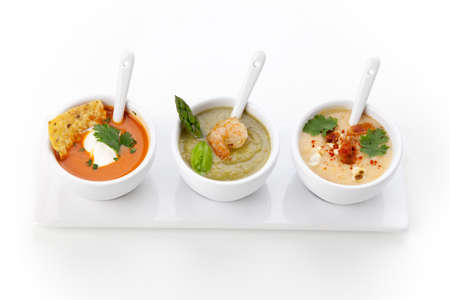 chilled: Closeup of three bowls of vegetable Tortilla-Chipotle soup, Cream of Asparagus soup, and Chilled Corn and Bacon soup over white background Stock Photo