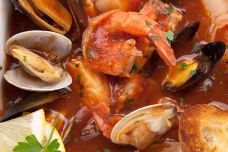 Bowl of Cioppino (seafood stew) with shrimps, scallops, crabs, clams, mussels, and fish.