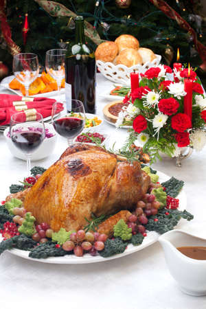Holiday-decorated table, Christmas tree, champagne, and roasted turkey  Stock Photo - 21565675