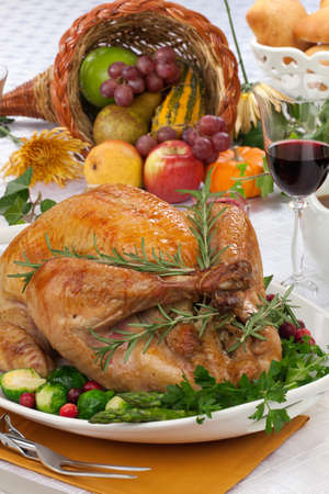 roast turkey: Garnished roasted turkey on fall festival decorated table with horn of plenty and red wine Stock Photo