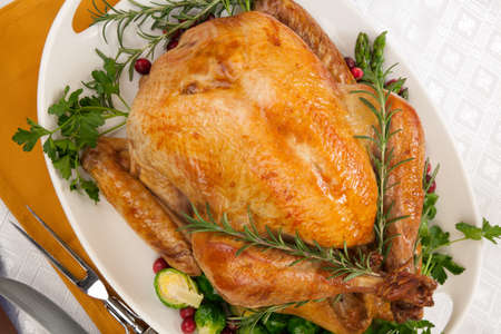 Garnished roasted turkey on fall festival decorated table with horn of plenty and red wine photo