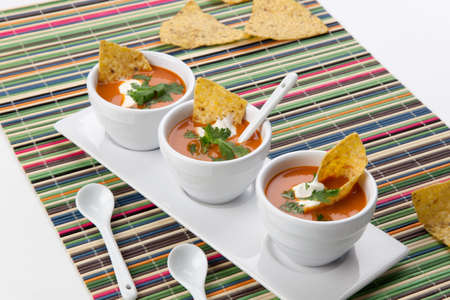 tomato soup: Closeup of three bowls of fresh hot delicious vegetable Tortilla-Chipotle soup garnished with sour cream, fresh cilantro, and tortilla chips Stock Photo