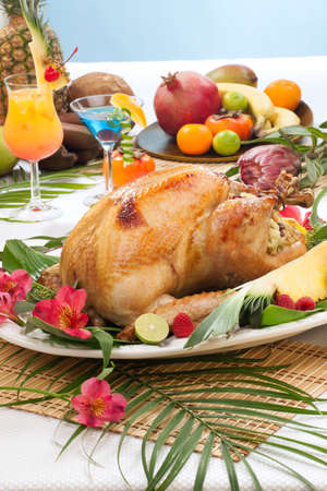 Garnished roasted turkey with tropical fruits, flowers, and refreshing cocktails for Thanksgiving