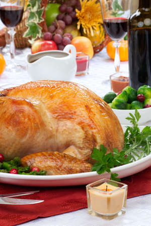 Garnished roasted turkey on fall festival decorated table with horn of plenty and red wine 写真素材