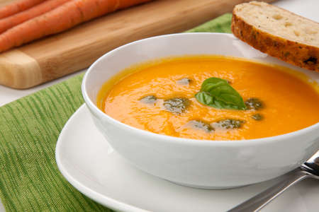 Creamy carrot soup with basil oil, garnished with herb whole wheat bread  Fresh carrots around