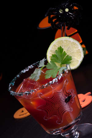 Closeup of Bloody Mary cocktail, garnished with lemon and parsley - Halloween drinks series photo