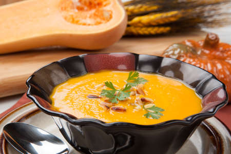 Hot delicious pumpkin soup in a bowl  Made from butternut squash  Garnished with roasted pine nuts, and fresh parsley  Stock Photo