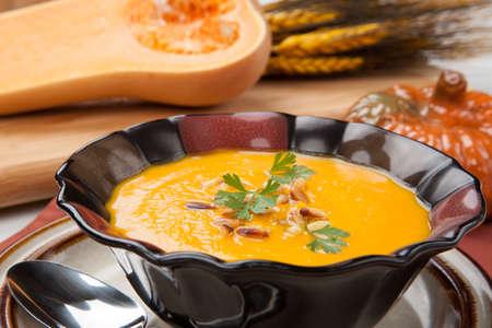 Warme heerlijke pompoen soep in een kom Gemaakt van butternut squash gegarneerd met geroosterde pijnboompitten en verse peterselie Stockfoto