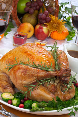 veggie tray: Garnished roasted turkey on fall festival decorated table with horn of plenty and red wine Stock Photo