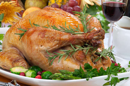 Garnished roasted turkey on fall festival decorated table with horn of plenty and red wine Stockfoto