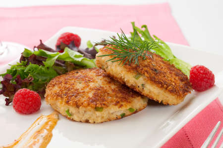 cangrejo: Dos pasteles de cangrejo aperitivo aderezado con salsa picante, ensalada verde y raspbery Foto de archivo