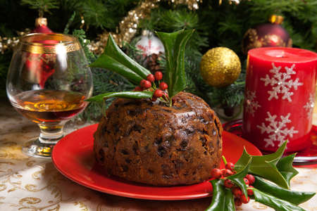 Holiday table with Christmas pudding decorated with holly twig, glass of brandy, ornaments, candles, and xmas tree  Standard-Bild