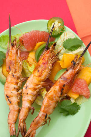 Close up of whole grilled large shrimps -scampi- on bamboo sticks served with spicy avocado-citrus salad.  photo