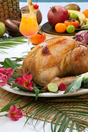 Garnished roasted turkey with tropical fruits, flowers, and refreshing cocktails for Thanksgiving.