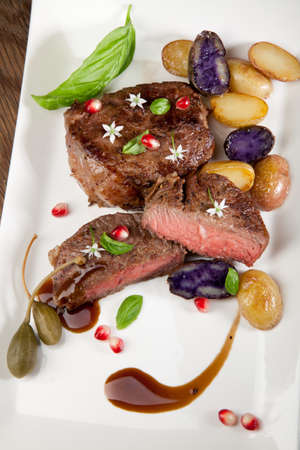 medium close up: Pan seared steak with fingerling potatoes, capers, pomegranate balsamic vinegar sauce, and fresh basil  Stock Photo