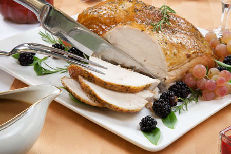 Carving Rosemary-basil rub roasted turkey breast garnished with grapes, blackberies, and fresh basil, and rosemary in fall themed surrounding  Stock Photo